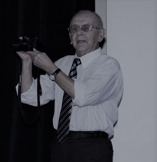 Na zdjęciu mężczyzna trzymający w ręku aparat fotograficzny.